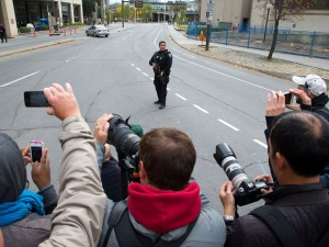 An employee of the Ottawa police department points his firearm at Canadian citizens.